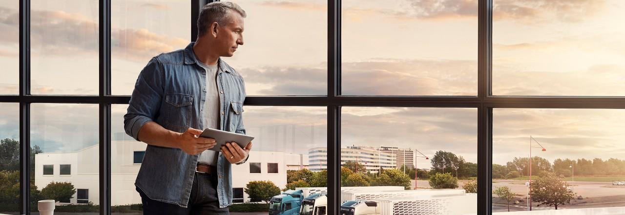 En mand med en tablet står ved et vindue og ser ned over sin lastbilflåde